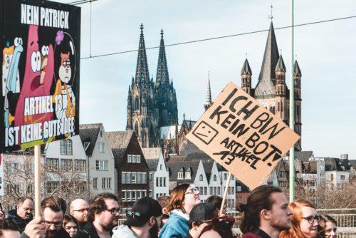 Eine Demo gegen Artikel 13 in Köln. Man sieht Protestschilder. Auf dem einen steht: Ich bin kein Bot! Artikel 13 (durchgestrichen)